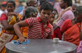 A boy cleans a table while working at an eatery in Hyderabad, India, June 11, 2016. A UNICEF report based on census data says the proportion of child workers in the 5-to-9-year age group jumped to 24.8 percent in 2011 from 14.6 percent in 2001.
