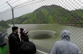 People stop to watch water flow into the iconic Glory Hole spillway at the Monticello Dam, Feb. 20, 2017, in Lake Berryessa, Calif. Water is flowing for the first time in over a decade into the 72-foot diameter hole due to the recent storms in Califo...