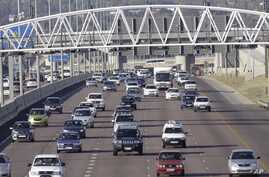 Cars stream underneath a gantry on a road to Pretoria, South Africa, May 4, 2012.