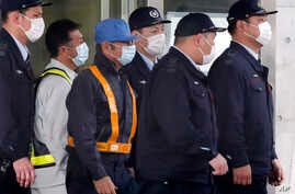 A masked man, center with blue cap, believed to be former Nissan Chairman Carlos Ghosn, walks out with security guards from Tokyo Detention Center in Tokyo, March 6, 2019, after posting 1 billion yen ($8.9 million) in bail.