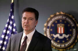 FBI Director James Comey takes questions from members of the media during a news conference in Boston, Nov. 18, 2014.