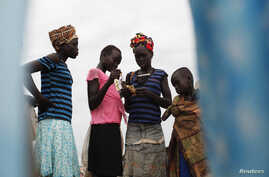 Girls check their ratio cards as they wait to receive food during food distribution in Minkaman, Lakes State, South Sudan, June 26, 2014.