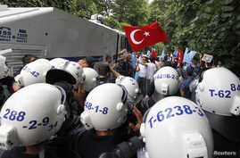 Turkish riot police try to stop ethnic Uighurs from marching to the Chinese Consulate during a protest against China, in Istanbul, Turkey, July 21, 2011.