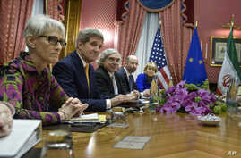 Energy Ernest Moniz, third left,  National Security Council point person on the Middle East Robert Malley, 2nd right,  and European Union Political Director Helga Schmid attend a meeting with Iranian officials at a hotel in Lausanne, Switzerland, Mar