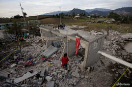 Residents stand next to debris after fireworks stored in a house exploded in San Isidro, Chilchotla, Mexico, May 9, 2017.