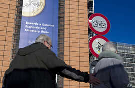 Two people are seen underneath a giant banner for the euro currency outside an EU summit in Brussels, Nov. 22, 2012.