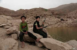 """In this July 30, 2018, photo, a 17 year-old boy holds his weapon in High dam in Marib, Yemen. Experts say child soldiers are """"the firewood"""" in the inferno of Yemen's civil war, trained to fight, kill and die on the front lines."""