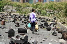 A boy walks on a street littered with cooking gas cylinders after a fire and explosions destroyed a nearby gas storage during clashes between fighters of the Popular Resistance Committees and Houthi fighters earlier today, in Yemen's southwestern cit