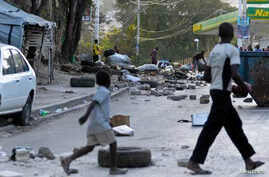 People walk through a litter-filled street after residents of a camp for people displaced by Haiti's January 2010 earthquake blocked streets after some tents were destroyed, Port-au-Prince, Feb. 15, 2013.