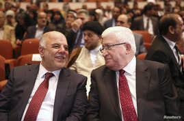 Iraq's new Prime Minister Haider al-Abadi (L) and Iraqi President Fouad Massoum speak during the session to approve the new government in Baghdad, Sept. 8, 2014.