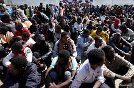 Illegal African migrants sit during a visit by U.N. officials at a detention camp in Tripoli, Libya, March 22, 2017.