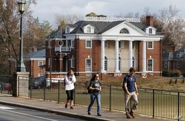 FILE - University of Virginia students walk to campus past the Phi Kappa Psi fraternity house in Charlottesville, Virginia, Nov. 24, 2015. Rolling Stone is casting doubt on the account it published of a young woman who says she was gang-raped at a Ph