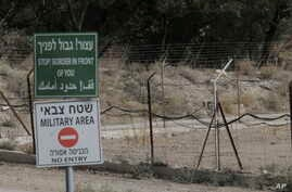 FILE - Signs warn of the border between Israel to Jordan, in the Jordan valley area called Baqura, Jordanian territory that was leased to Israel under the 1994 peace agreement between the two countries, Oct. 22, 2018.