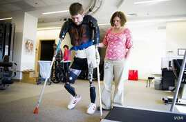 Former Marine Sgt. John Peck is seen walking on artificial limbs before having a double arm transplant. (John Peck)