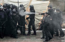 Protesters, right, use tear gas as they clash with police during a rally outside the parliament building in Kyiv, Ukraine, Jan. 16, 2018.