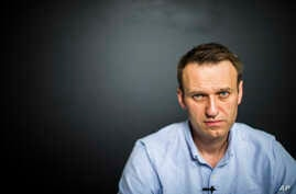 In this photo provided by Alexei Navalny's campaign, Russian opposition leader Alexei Navalny records a video for his YouTube channel in his office in Moscow, Russia, July 7, 2017.