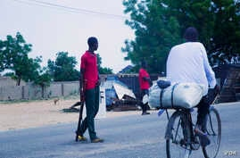 A cyclist rides past Civilian Joint Force members who are patrolling the streets looking for Boko Haram fighters. Maiduguri, Nigeria. (C. Oduah for VOA)