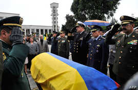 Commanders of the Police and Armed Forces of Colombia salute by the coffin of lieutenant colonel Alfredo Ruiz next to his wife Daissy Esperanza (2-L) during his funeral in Bogota, Colombia, on June 14, 2015. Ruiz died alongside police officer Juan Da