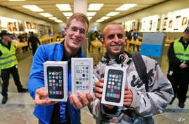 First customers of the Apple store in Oberhausen are all smile with their new iPhones in hand as they leave the store after the start of the new iPhone sale in Oberhausen, Germany, Sept. 20, 2013.