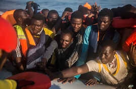 In this Thursday, July 28, 2016 photo, about 150 sub-Saharan refugees and migrants receive life jackets as they aboard an overcrowded rubber boat and wait to be assisted by an NGO during a rescue operation on the Mediterranean Sea, about 23 kilometer