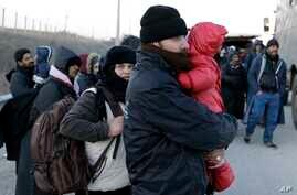 Refugees and migrants wait for police and military vans on a highway near the Greek village of Thourio, at the Greek-Turkish border, Jan. 24, 2016. The migrants told police they were part of a group of 130 who crossed the Evros River between Greece a