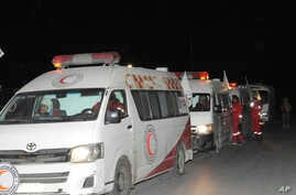Photo released by the Syrian official news agency SANA, shows members of the Syrian Arab Red Crescent gathering near their ambulances during a human evacuation of sick and wounded people from the eastern Ghouta, near Damascus, Dec. 28, 2017.