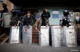 Pro-Russia protesters stand guard at the entrance of the district council building in Donetsk, eastern Ukraine, May 4, 2014.