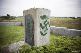 FILE - A monument with Nazi swastikas painted over it is seen in Jedwabne, Poland, Sept. 1, 2011.