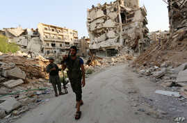 Rebel fighters walk in front of damaged buildings in Karam al-Jabal neighbourhood of Aleppo on August 26, 2014.
