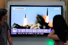 South Koreans watch a TV news program showing the missile launch conducted by North Korea, at Seoul Railway Station, Seoul, June 26, 2014.