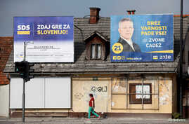 A woman walks under election posters of the Slovenian Democratic Party ahead of elections in Ljubljana, Slovenia, May 31, 2018.