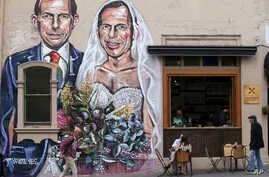 A mural depicting former Australian Prime Minister Tony Abbott as both a groom and a bride is displayed on a cafe wall in Sydney, Sept. 12, 2017. More than 16 million Australian voters will receive ballots requesting their opinion on whether same-sex