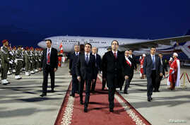 Tunisia's Prime Minister Youssef Chahed, front right, walks with his French counterpart Manuel Valls, left, upon his arrival at Tunis airport in Tunis, Tunisia, Nov. 28, 2016.