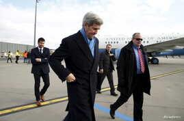 """U.S. Secretary of State John Kerry (C) steps from his plane upon his arrival in Vienna, Austria, on what is expected to be """"implementation day,"""" the day the International Atomic Energy Agency (IAEA) verified that Iran has met all conditions under the"""
