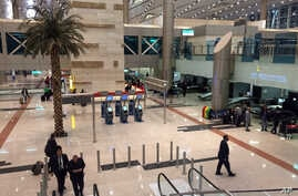 Airport staff gather near a security checkpoint at Cairo International Airport, March 21, 2017.