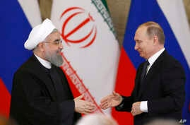 Russian President Vladimir Putin, right, shakes hands with Iranian President Hassan Rouhani during a joint news conference at the Kremlin in Moscow, Russia, Tuesday, March 28, 2017.