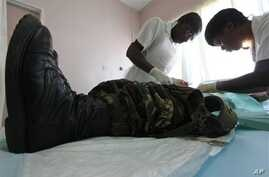 In this Oct. 28, 2010 photo, a doctor and a nurse perform a circumcision procedure on a Zimbabwean soldier at a local clinic in Harare, Zimbabwe. The U.S. Agency for International Development is leading a war on AIDS that may help save hundreds of th