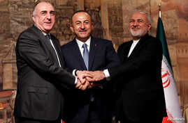 Turkish Foreign Minister Mevlut Cavusoglu, center,  poses with his counterparts Elmar Mammadyarov, left, of Azerbaijan and Javad Zarif of Iran following a news conference in Istanbul, Turkey, Oct. 30, 2018.