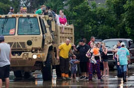 Members of the Louisiana Army National Guard unload people at a rally point after they were rescued from rising floodwater near Walker, La., after heavy rains inundated the region, Sunday, Aug. 14, 2016.