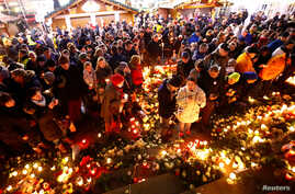 People hold candles at the memorial site of last year's truck attack in a Christmas market, which killed 12 people and injured many others, at Breitscheidplatz square in Berlin, Dec. 19, 2017.
