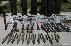 FILE - Weapons and ammunition seized are presented to the media along with insurgents suspected of being from the Haqqani network at the National Directorate of Security (NDS) headquarters in Kabul, May 30, 2013.