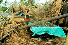 A resident retrieves belongings from his destroyed house after Typhoon Nock-Ten hit Malinao, Albay in central Philippines, Dec. 26, 2016.
