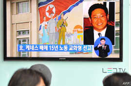 Passersby watch a local television broadcast in Seoul on May 2, 2013 showing a report and picture of Kenneth Bae (R), a Korean-American tour operator detained in North Korea, against the background of a North Korean flag painted on the wall of a buil