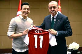 Turkey's President Recep Tayyip Erdogan, right, poses for a photo with Turkish-German Arsenal soccer player Mesut Ozil in London, May 13, 2018.