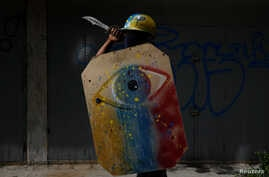 """A demonstrator holding a rudimentary shield and a knife poses for a picture before a rally against Venezuelan President Nicolas Maduro's government. """"I protest because the situation is very tough and we are going hungry. We really need a change."""""""