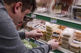 """A worker removes expired food in a local supermarket in Brussels on  Jan. 16, 2017.  The European Court of Auditors chided the European Union's executive branch in a report, """"Combating Food Waste,"""" that decries the bloc's lack of effort in reducing t"""