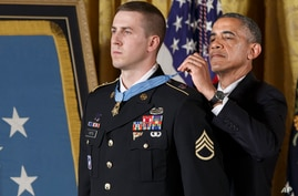 President Barack Obama bestows the Medal of Honor, to Ryan M. Pitts, 28, a former Army staff sergeant who fought off enemy fighters during one of the bloodiest battles of the Afghanistan war despite his own critical injuries, in the East Room of the