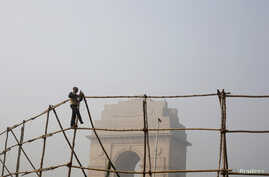 A laborer dismantles scaffoldings near the India Gate war memorial on a smoggy day in New Delhi, February 2013.