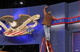 A worker cleans lint off the background of the stage for a debate at the University of Denver ,Tuesday, Oct. 2, 2012, in Denver. President Barack Obama and Republican presidential candidate and former Massachusetts Gov. Mitt Romney will hold their fi...