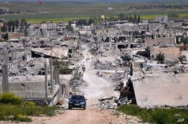 FILE - A car passes in an area that was destroyed during the battle between the U.S.-backed Kurdish forces and the Islamic State fighters, in Kobani, north Syria, April 18, 2015.